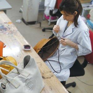 手作業で修復する女性